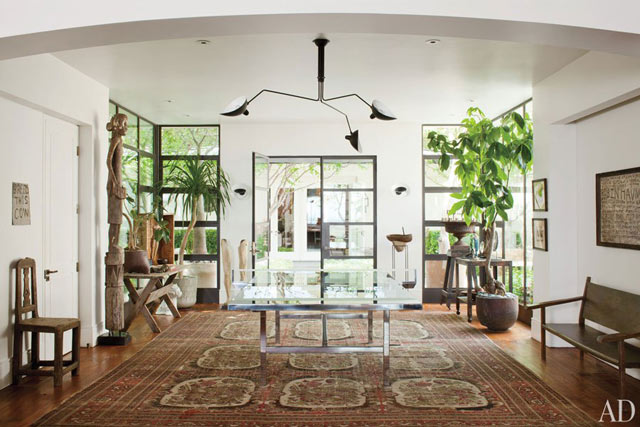 A glass Ping-Pong table is a fun edition to the entrance hall, while the modern chandelier, plants and rug tie the room together.
