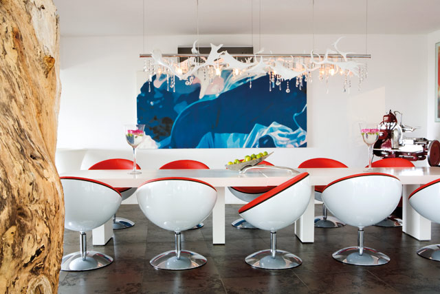 The dining area is a post modern space with its retro tub chairs, white modernist plinth tables and custom designed reindeer-antler and glass chandelier.