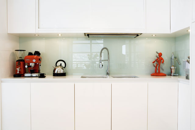 The apartment's all-white theme continues into the kitchen with funky kitchen appliances providing a splash of strong colour. The glass backsplash is available from GlassKote