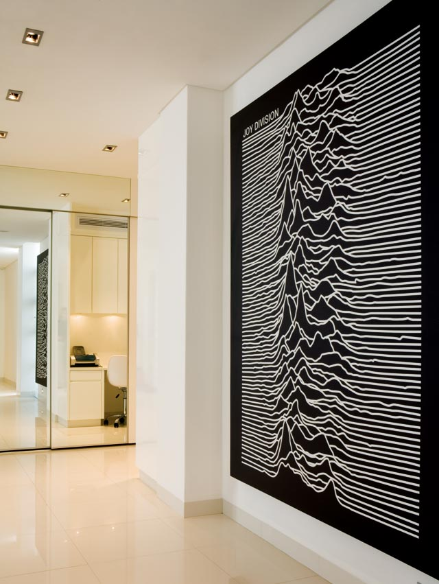 An oversized print of a Joy Division album cover depicting an abstraction of sound waves takes centre stage in the entrance area.  Full-height mirrored sliding doors reflect  a cleverly tucked-away work area at the back