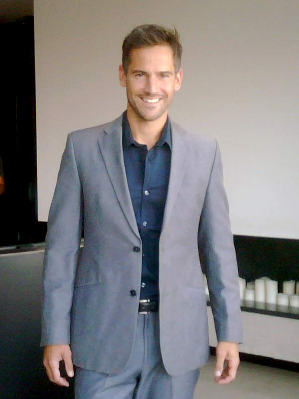Janez wearing grey C'Squared suit, and navy shirt from Blue Collar White Collar